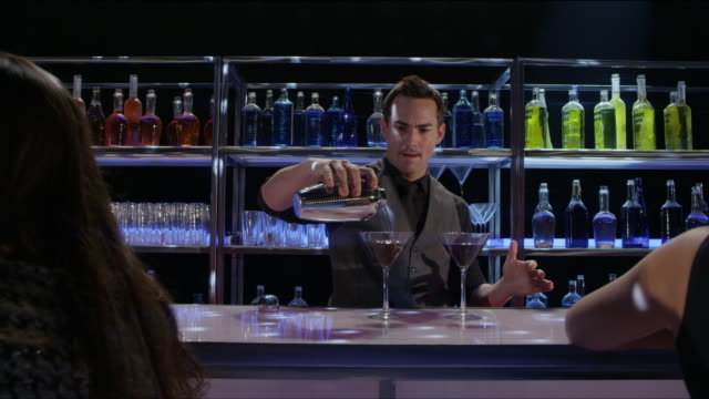 MS bartender pours drinks and camera pans to young couple who mingle and toast - nightclub bar scene