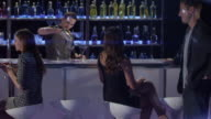 WS bartender pours drinks and serves to young couple who mingle and toast - nightclub bar scene