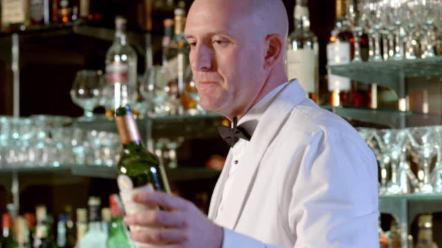 MS bartender pours red wine from bottle into wine glass sitting on bar counter in upscale bar