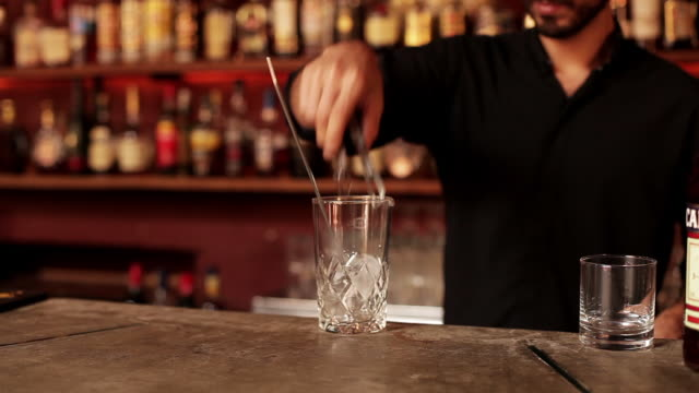 Bartender putting ice cube in mixing glass