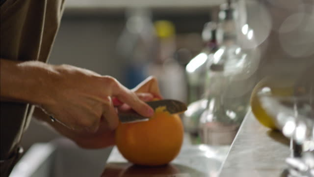 Bartender slices orange peel for specialty mixed drink