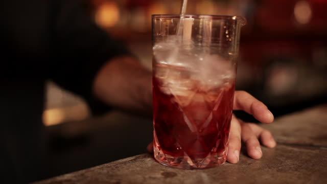 Bartender stirring negroni cocktail
