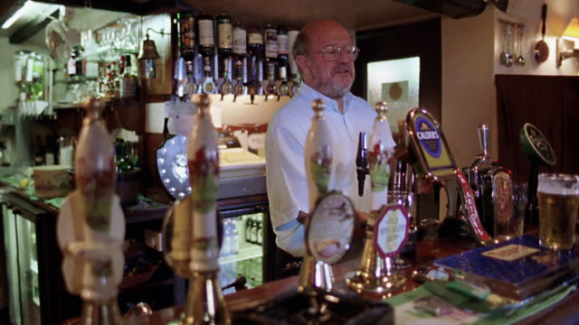 PAN bartender talking to customer while serving beer to other customer in pub / London, England