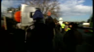 Barton Moss antifracking protest Police leading group of protesters from road / Lorries towards from road past protesters and protesters chanting...