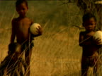 Basarwa children walking along grassland carrying patterned ostrich eggs