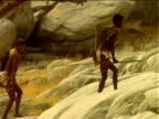Basarwa tribesmen holding spears walk up rocks, Botswana