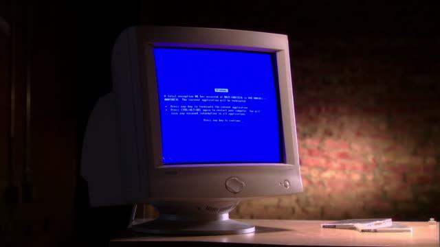 MS baseball bat hitting and breaking computer monitor displaying blue Windows error message on desk