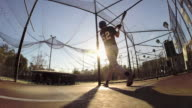 A baseball player practicing at the batting cages. - Slow Motion