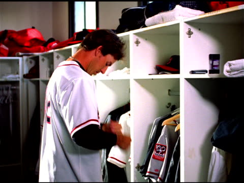 Baseball player pulls on jersey in locker room