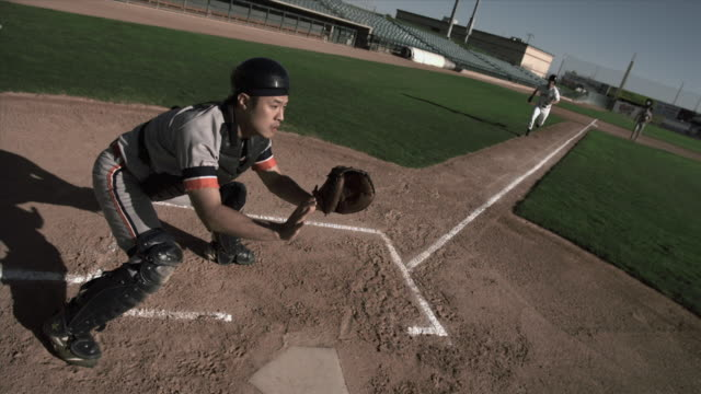 SLO MO HA WS Baseball player sliding into home plate as catcher catches ball and tags him / Lancaster, California, USA