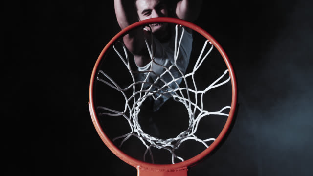 SLO MO of basketball player doing a slam dunk shot
