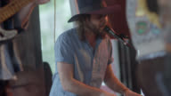 Bassist plays as keyboardist sings into microphone with rock band in Austin bar