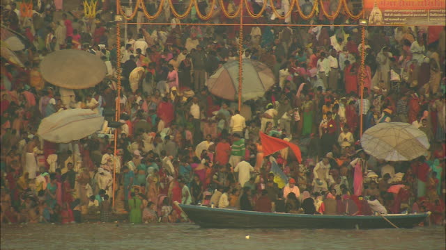 Bathers wash in the Ganges as hundreds wait their turn and others ride in boats.