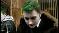 Batman fans audition for new show 'Batman' music overlaid SOT Man applying greasepaint to face as reads lines in queue Fans queuing outside building...