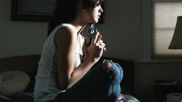 battered woman sitting on a bed holding a handgun up to her chin