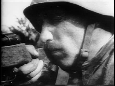 Battlefield fighting between Russian Army and Nazis / Russian soldier throws hand grenade / German soldiers advance down hill / Russian fires machine...