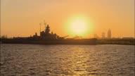 AERIAL Battleship USS Alabama backlit by setting sun, downtown skyline in background, Mobile, Alabama, USA