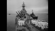 / Battleship USS Missouri pulling into Tokyo Bay / Fleet Admiral Chester William Nimitz comes on deck and salutes his troops who are at attention in...