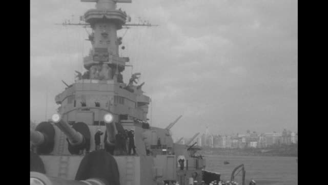 Battleship with military band on board fires its guns in salute during Navy Day celebration