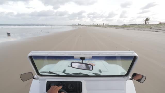 WS, POV A beach buggy drives along a sandy beach / Natal, Brazil