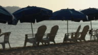 MS Beach chairs and umbrellas at water's edge / Acapulco, Guerrero, Mexico
