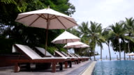 Beach chairs near swimming pool in tropical resort