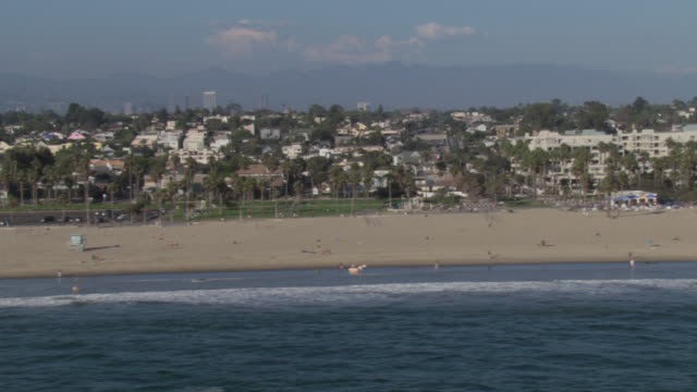 AERIAL Beach front properties with palm trees, Santa Monica pier, and mountains in the distance / Santa Monica, California, United States