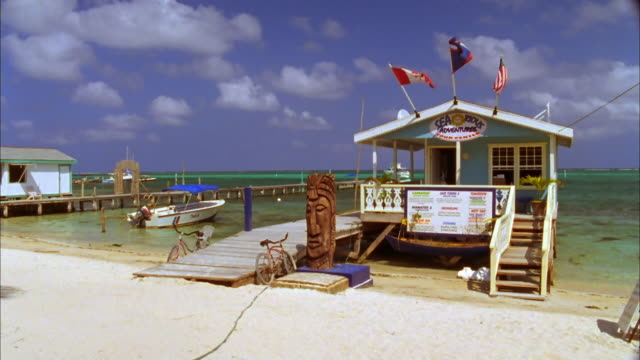 Beach hut with flying flags attached to jetty, Belize Available in HD.