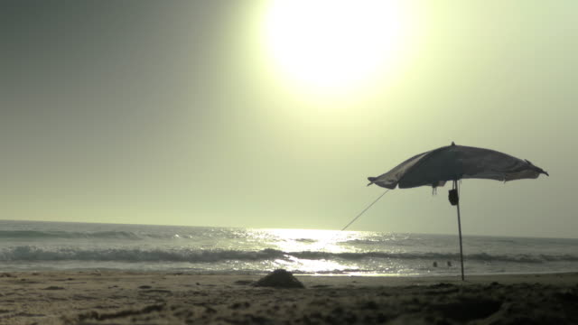 beach umbrella with wind with people having a bath in the sea in cadiz spain