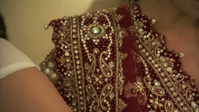 Beads decorate an embroidered gown.