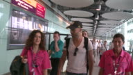 A beaming Oscar Pistorius walks with two Heathrow staff as arrives at the airport for London olympics