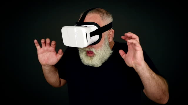 Beard Elderly man frightened in virtual reality glasses on a black background