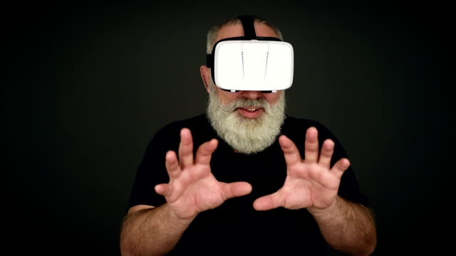 Beard Elderly man scared in virtual reality glasses on a black background