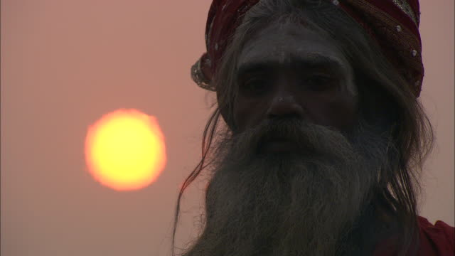 A bearded and turbaned man stands in the smoke of a cremation ceremony as the sun rises in India.