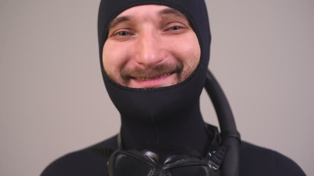 bearded diver smiling on a gray background
