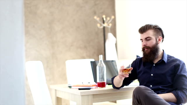 Bearded hipster is drunk at work in the office