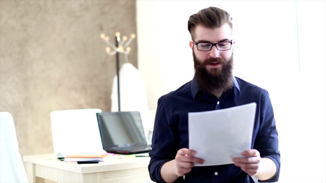 Bearded hipster read the papers in offices