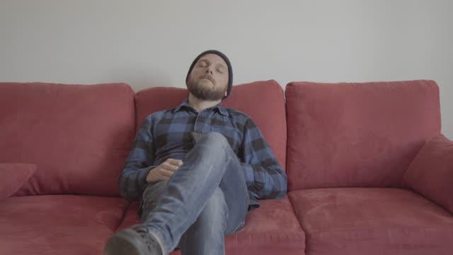 Bärtiger Mann zu Hause auf einem roten Sofa: verschlafene Stimmung