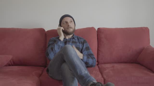 Bärtiger Mann zu Hause auf einem roten sofa