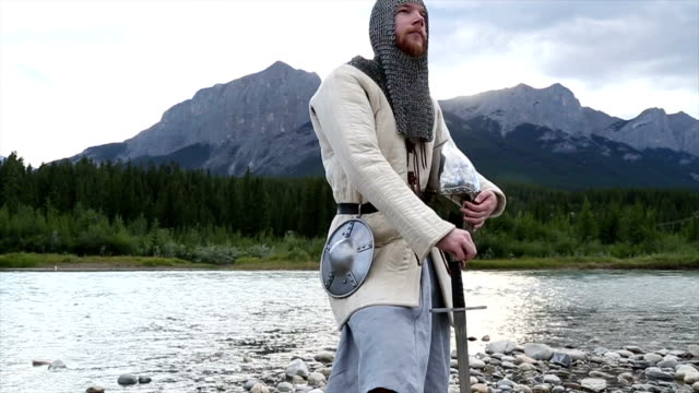 Bearded man in medieval/viking costume pauses by river