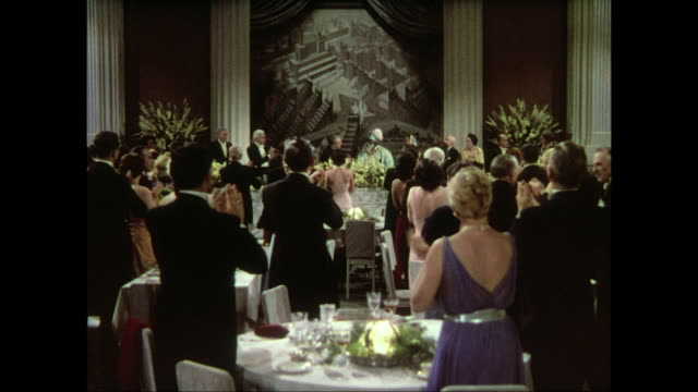Bearded man in traditional dress receives standing ovation in packed dining room