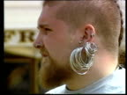 Bearded man with mohican and lots of earrings turns towards camera
