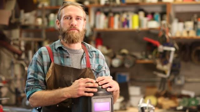 Bearded metal fabricator working in his shop