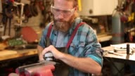 Bearded metal fabricator working in his shop