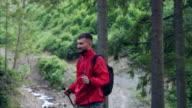 Bärtiger junger Mann mit Stöcken Wandern entlang