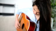 Beatiful girl playing acoustic guitar