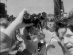 Beatlemania shots of Beatles fans waiting for their idols girls with binoculars looking up at King Edward Sheraton Hotel windows / Several CUs of...