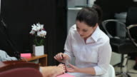 Beautician varnishing toenails