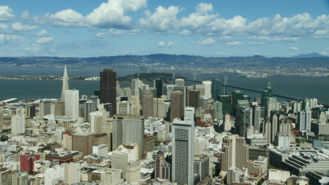 Beautiful aerial shot of the city of San Francisco, pulling out from view of skyscrapers to wide shot of city and bay.