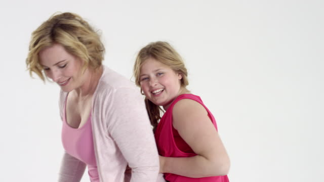 beautiful and happy plus-size mum and daughter having great fun - on rotating turntable